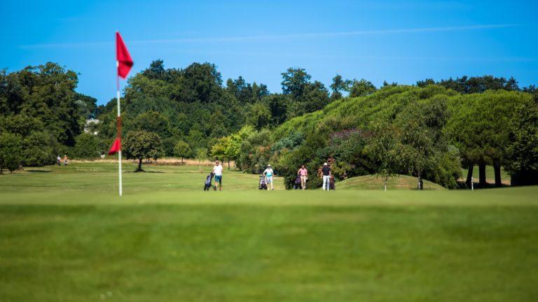 Golf des Sables d'Olonne golf course golfers golf game Blue sky Green red flag